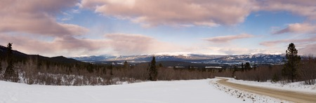 Sunset clouds over Road in winter landscape panorama outside wilderness city of Whitehorse, Yukon Territory, Canada