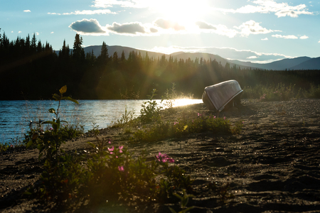Canoe turned over on shore of Nisutlin River in boreal forest taiga wilderness of Yukon Territory, Canada 写真素材