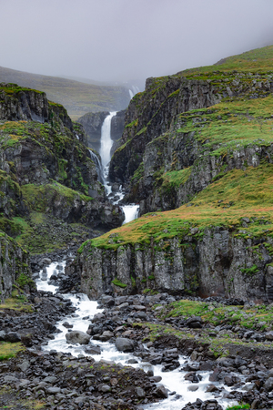 Small waterfall of stream without name snaking through barren mountain side landscape near Reydarfjordur in East Iceland, IS, Europe