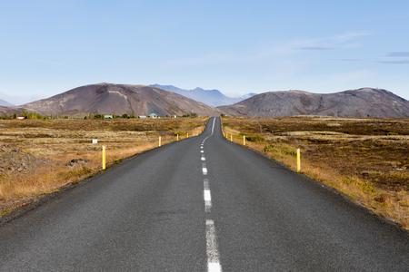 Paved road in barren volcanic landscape leading to distant mountain range in Golden Circle Region, Iceland, IS, Europe 写真素材 - 118488281