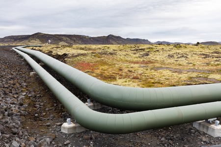 Insulated metal pipeline as part of geothermal energy generation infrastructure in barren volcanic landscape of Iceland, IS, Europe 写真素材