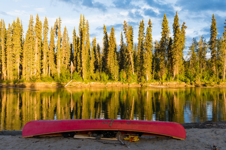Red canoe turned over on shore of Nisutlin River, Yukon Territory, Canada, on a beautiful summer evening in boreal forest taiga 写真素材