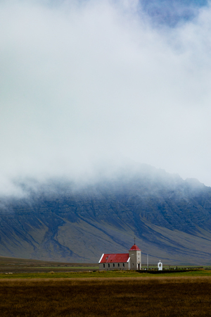 Small church building in fertile landscape before towering mountains mostlry hidden in foggy clouds, Western Region of Iceland, IS, Europe