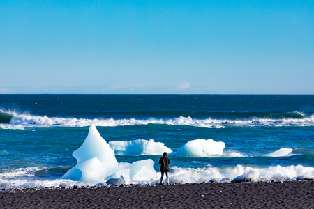 Person on black sand Diamond Beach watching glacier ice in Atlantis Ocean surf washed ashore from glacier lagoon of Jokulsarlon, Iceland, IS, Europe