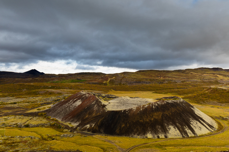 Black volcanic lava rock of Grabrok volcano crater cone in sparse vegetation tundra landscape of Iceland, IS, Europe 写真素材 - 118488326