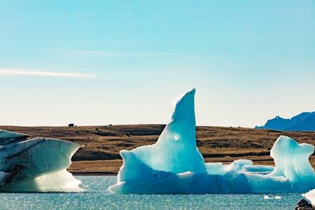 Bizarre shapes of blue icebergs calved off Vatnajokull glacier floating in Jokulsarlon glacier lagoon, Iceland, IS, Europe 写真素材 - 118488329