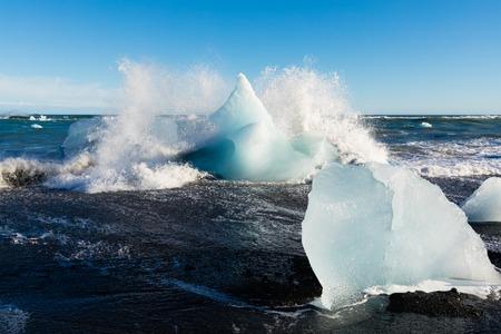 Surf crashing into ice chunks washed on Diamond Beach near glacier lagoon of Jokulsarlon, Iceland, IS, Europe 写真素材 - 118488330