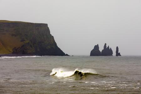 Breaking wave and Reynisdrangar rock formations offshore black volcanic Reynisfjara sand beach at Atlantic ocean coast near Vik, Iceland, IS, Europe 写真素材 - 118488336