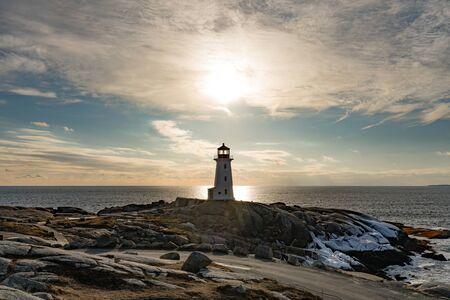 Famous tourist destination Peggys Cove Lighthouse on granite rock cliffs overlooking calm Atlantic Ocean, Nova Scotia, NS, Canada