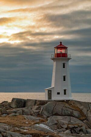 Famous tourist attraction Peggys Cove Lighthouse on granite rock cliffs overlooking calm Atlantic Ocean, Nova Scotia, NS, Canada Фото со стока