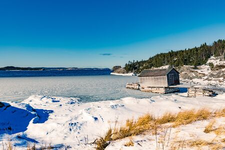 Vecchia capanna di legno della fase di pesca nella calma del paesaggio invernale della baia dell'isola del nuovo mondo, Terranova, NL, Canada