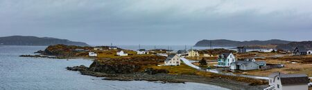 Bad rainy weather at North Atlantic Ocean shoreline with traditional outport fishing town houses of Twillingate, Newfoundland, NL, Canada Reklamní fotografie - 133997794