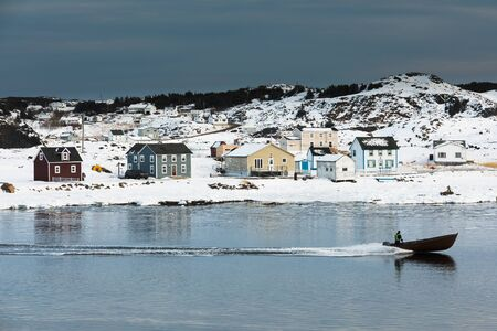 Motor boat enters Durrell Harbour of outport town of Twillingate passing traditional wooden saltbox residential houses in winter, Newfoundland, NL, Canada