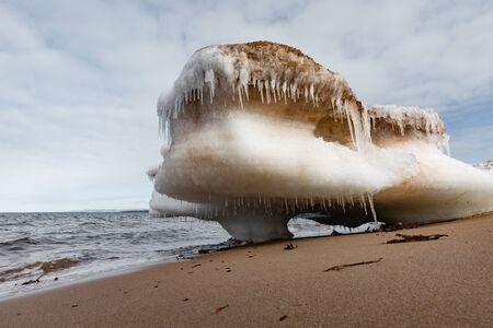 Bizarre chunk of ice floe beached on sand of Melmerby Beach Provincial Park near Merigomish, Nova Scotia, NS, Canada Reklamní fotografie - 133997844