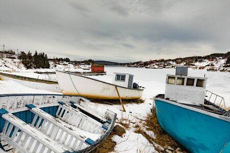 Small fishing boats beached for the winter at frozen North Atlantic Ocean bay, Newfoundland, NL, Canada