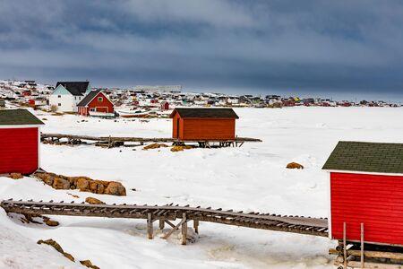 Fishing stage shacks of outport fishing village of Joe Batt's Arm at shore of frozen North Atlantic Ocean on Fogo Island, Newfoundland, NL, Canada Reklamní fotografie - 133997847