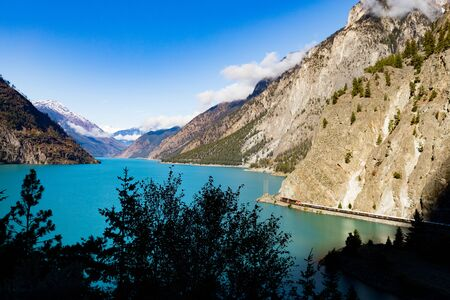 Tiny freight train in grand mountain landscape of Seton Lake near Lillooet, British Columbia, BC, Canada