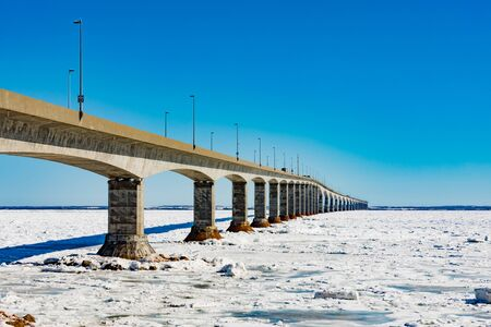 Concrete structure of Confederation Bridge spans frozen Atlantic Ocean between New Brunswick and Prince Edward Island Canada Reklamní fotografie - 133997855
