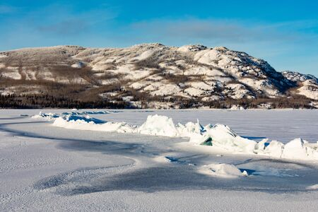 Tension stress between ice floes causes pressure ridge on frozen Lake Laberge, Yukon Territory, Canada