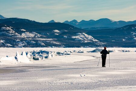 Cross-country skier exploring pressure ridge caused by tension stress between ice floes in frozen winter wonderland landscape of  Lake Laberge, Yukon Territory, Canada