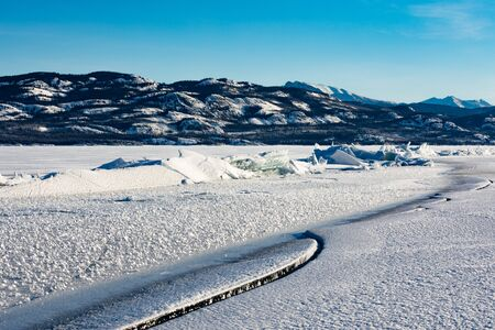 Pressure ridge caused by tension stress between ice floes on frozen Lake Laberge, Yukon Territory, Canada Stock fotó