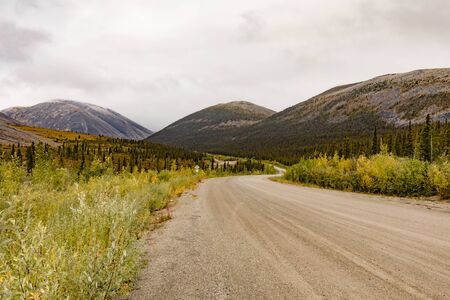 Dempster Highway gravel dirt road in subarctic terrain of Ogilvie Mountains, Yukon Territory, YT, Canada 写真素材 - 132018928