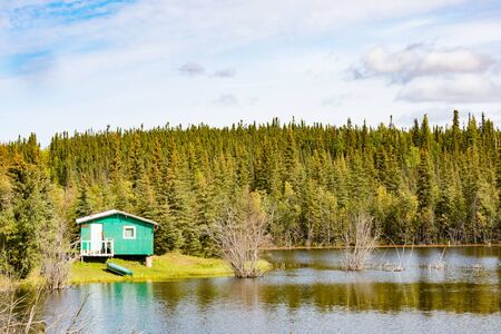 Small remote wilderness cabin at lake front in Peel River valley of Northwest Territories, NWT, Canada
