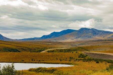 Dempster Highway crossing autumn colors of arctic tundra landscape of Richardson Mountains in Northwest Territories, NWT, Canada