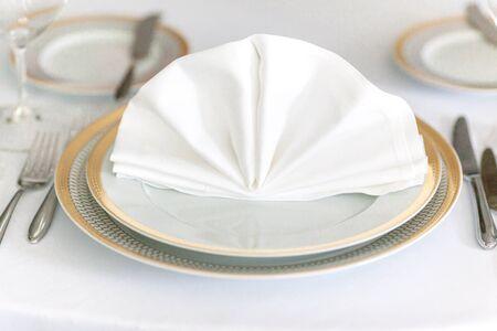servilleta de papel: white plate yellow canvas tablecloth napkin serviette fork Foto de archivo