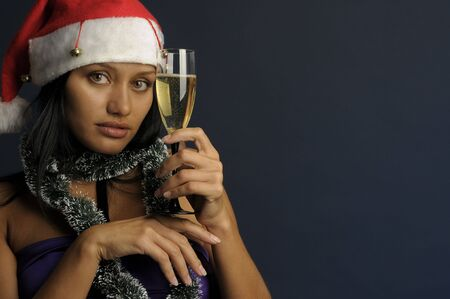 beautiful exotic woman in the red hat with the glass of champagne into Christmas photo