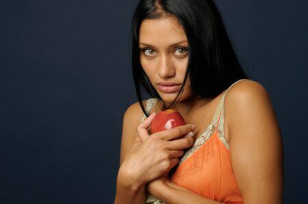 fateful: Beautiful Exotic Woman is eating and holding the apple Stock Photo
