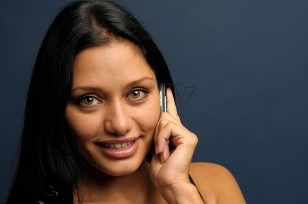 Beautiful exotic businesswoman is talking to mobil phone and smiling. photo