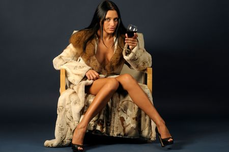 beautiful woman dressed in furs is sitting on the chair and drinking wine photo