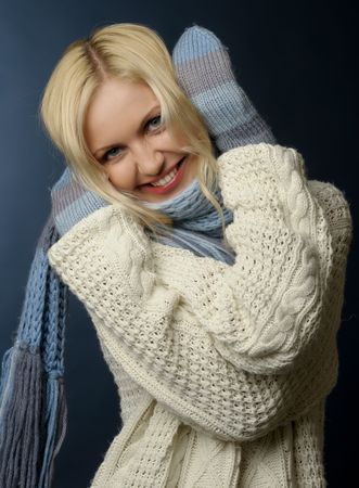 Beautiful blonde girl in winter clothes.She is dressed in sweater, scarf and mittens. Stock Photo - 3948460