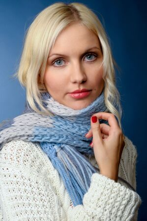 Beautiful blonde girl in winter clothes.She is dressed in sweater, scarf and mittens. Stock Photo - 3948458