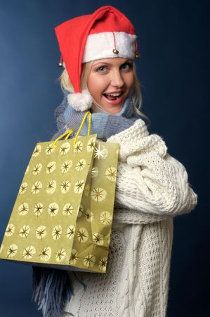 Beautiful blonde girl in winter clothes, santa hat with gift bag photo