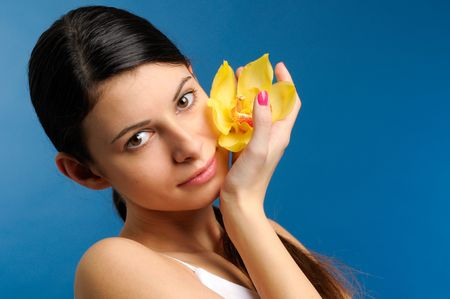 Portrait of the beautiful girl with yellow orchid photo