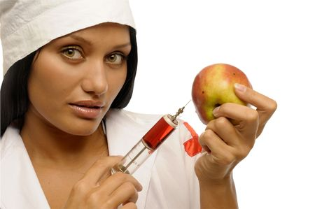 Young beautiful girl in doctor clothes with syring� and apple. photo