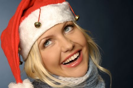 Beautiful blonde girl in scarf and santa hat photo