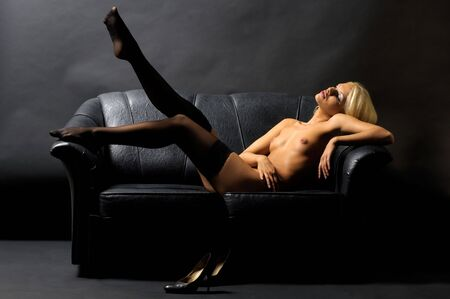 Beautiful nude blond girl is lying on the sofa and looking at her legs