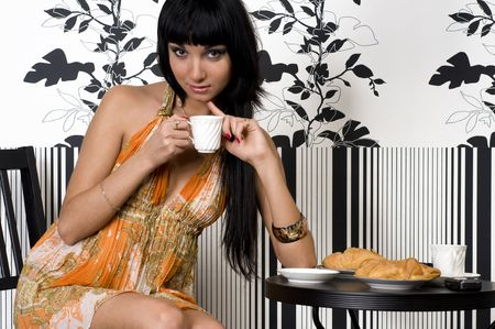 Beautiful girl is sitting in the cafe and drinking coffe with croissant