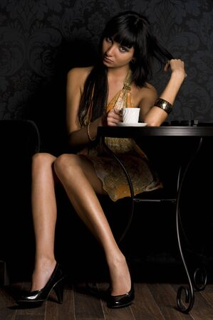 Beautiful girl is sitting in the cafe and  drinking coffe photo