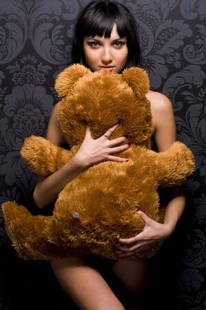Beautiful naked girl is holding the teddy bear photo