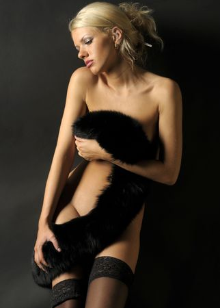 Beautiful blond naked girl in stockings with fur photo