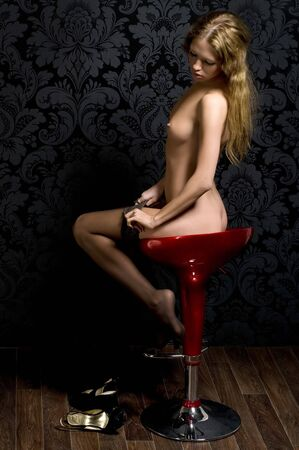 fine art nude: Beautiful blond girl is sitting on the bar chair and undressing Stock Photo