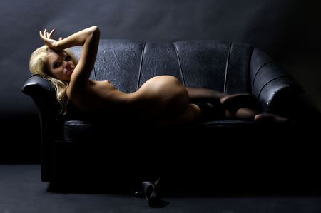 Beautiful blond naked woman is lying on the sofa Stock Photo