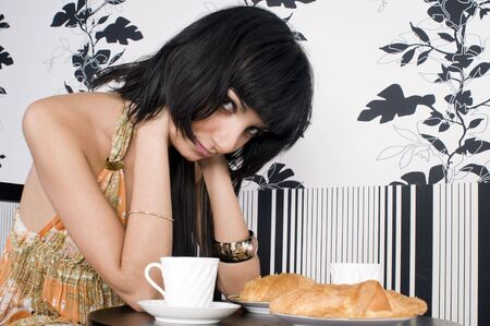 Beautiful brunette girl is waiting for someone in the cafe photo