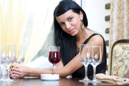 Beautiful woman is sitting in restaurant with glass of red wine Stock Photo - 4524213