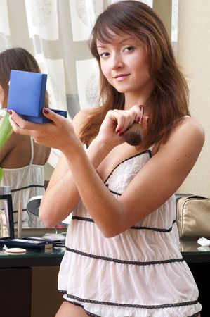 Beautiful young woman is making up  photo