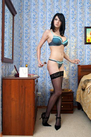 Beautiful undressed woman is making up in her bedroom Stock Photo